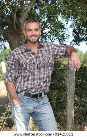 Man leaning on fence - stock photo