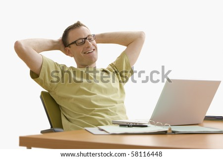 Man leans back in his chair while working on his laptop at home.  Horizontal shot.  Isolated on white. - stock photo