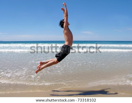 man leaping into air at the beach