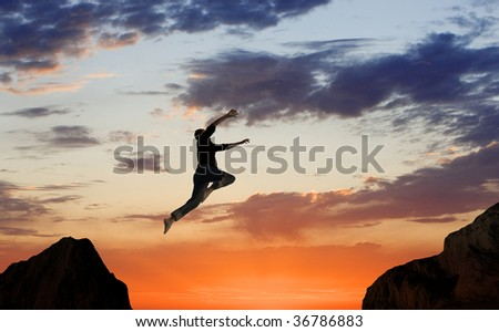 Man Leaping Mid-air on Mountainside - stock photo
