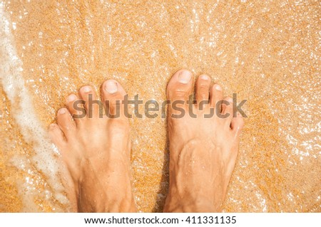 man legs in the sand as relax background