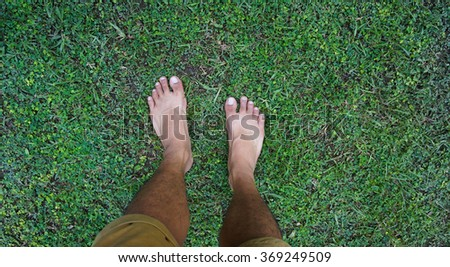 man legs walking on green grass