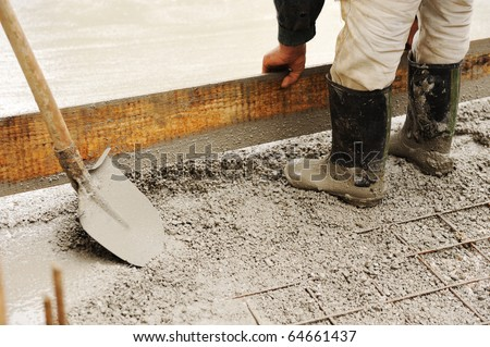 Man leveling concrete slab - stock photo