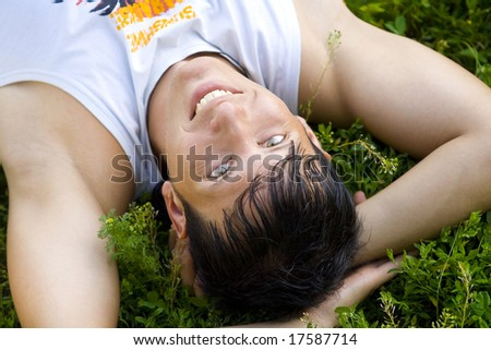 man lie on grass in the park - stock photo