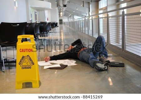 Man lies on the wet floor on which he slipped in spite of caution sign, selective focus on man's head - stock photo