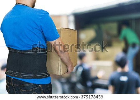 Man lift heavy carton wearing support belt for protect his back, blurred background of worker lift cartons