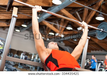 Man lifting a weight in a fitness club - stock photo