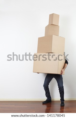 Man lifting cardboard boxes in apartment interior - stock photo