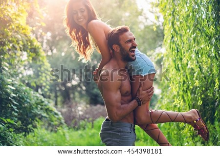 Man lifting his girl up and laughing - stock photo