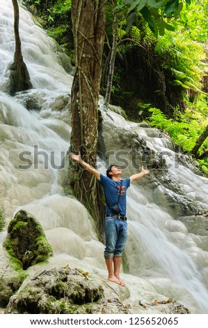 Man lifting his hands at waterfall, Praise for GOD. - stock photo