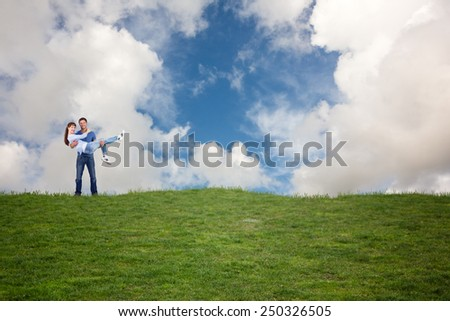 Man lifting up his girlfriend against blue sky with white clouds - stock photo