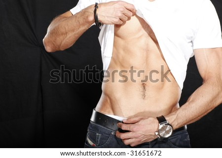 Man lifting up shirt to show off his rock hard abs - stock photo