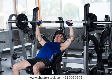 Man lifting weight in the sports club - stock photo
