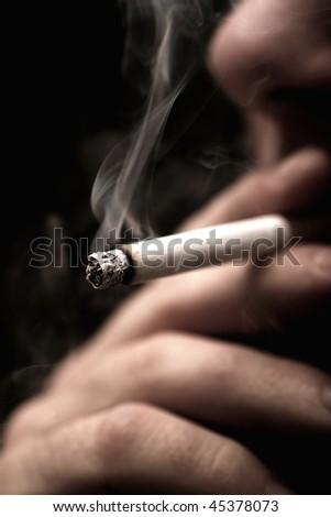 Man lighting a cigarette over black - stock photo