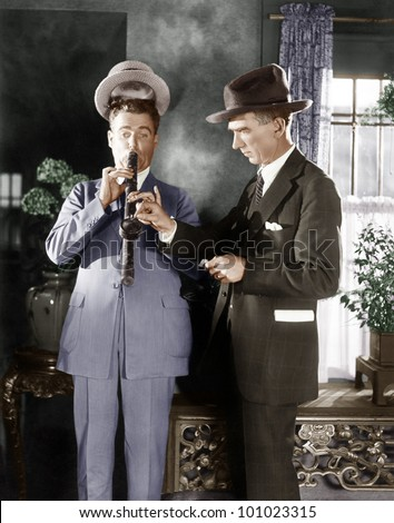 Man lighting a long pipe while his hat is lifting up from his head