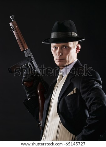 Man like a chicago gangster in suit and light waistcoat  with submachine gun - stock photo