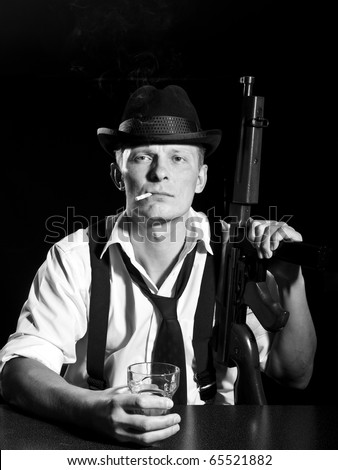 Man like a chicago gangster posing with submachine gun - stock photo
