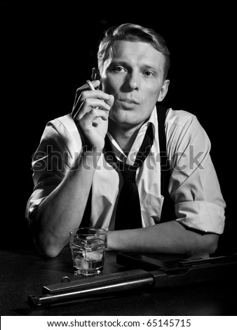 Man like a chicago gangster rests with glass of drink and submachine gun - stock photo