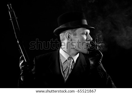 Man like a chicago gangster smokes a cigar - stock photo