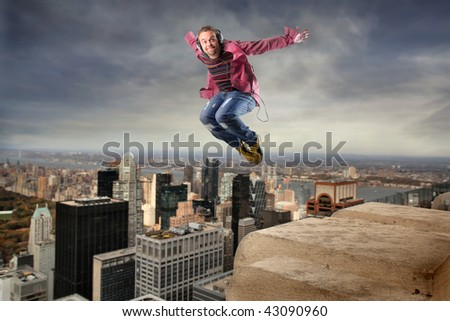 man listening music and jumping over NY city - stock photo
