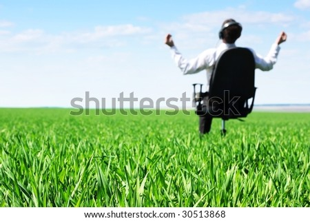 Man listening music in chair on green meadow - stock photo