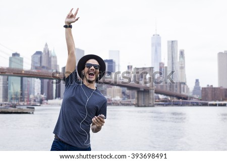 Man listening music with a rock sign hand up in Brooklyn, New York - stock photo