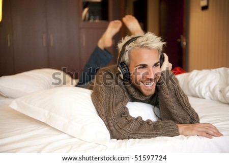 Man listening music with headphones at home. - stock photo