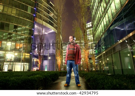 man listening music with headphones in a city street - stock photo