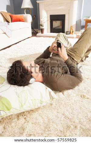 Man Listening To MP3 Player On Headphones Relaxing Laying On Rug At Home - stock photo