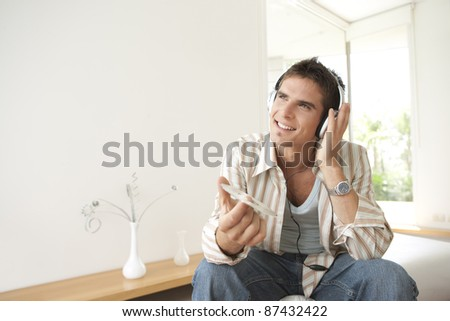 Man listening to music at home, using headphones - stock photo