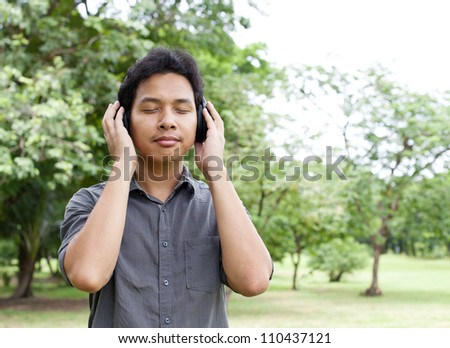 Man listening to music in the park - stock photo
