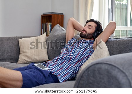 man listening to music relaxing on sofa couch in home living room - stock photo