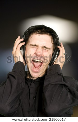 man listening to plaisant music over black background
