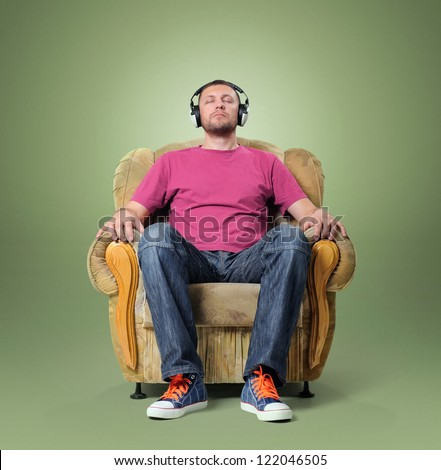 Man listening to relaxing music while sitting in a chair - stock photo