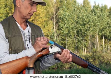 Man loading cartridges into a shotgun - stock photo