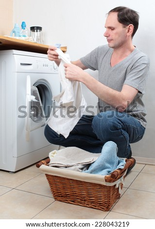 Man loading clothes into washing machine