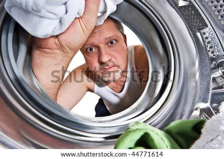 Man loading cloths to washing machine. View from inside the washing machine. - stock photo
