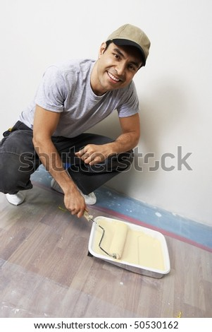 Man loading paint roller in tray indoors - stock photo