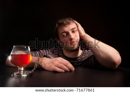 Man locked to glass of alcohol by handcuffs