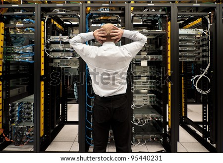 Man looking astonished in a network data center. - stock photo