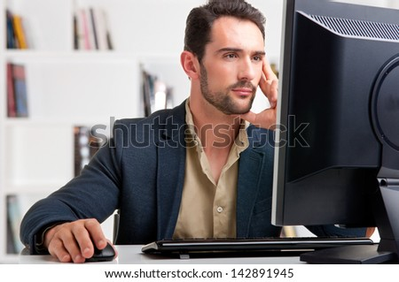 Man looking at a computer screen, thinking about the job at hand - stock photo