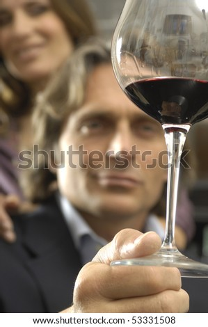 Man looking at a glass of wine