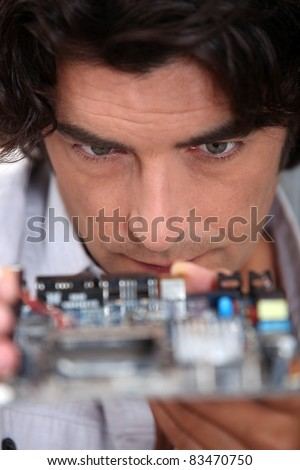 Man looking at a motherboard - stock photo