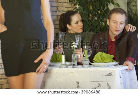 man looking at a nice girl passing by while dining out with his girlfriend in restaurant - stock photo