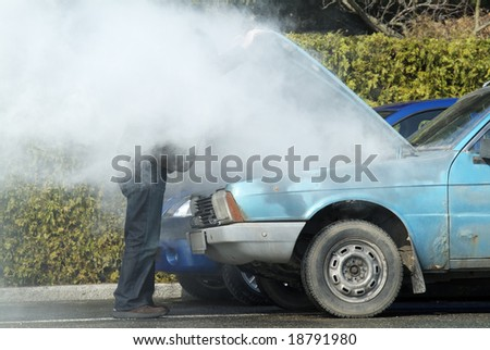 Man looking at a smoking engine in his car - stock photo
