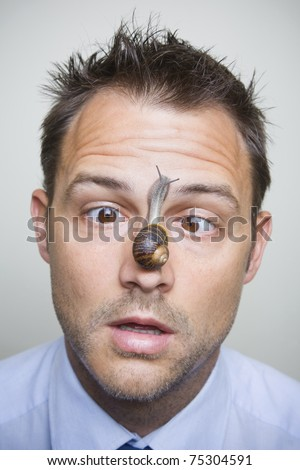 Man looking at a snail sliding up his nose.