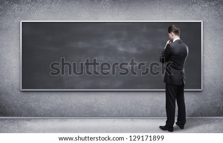 man looking at blackboard in interior - stock photo