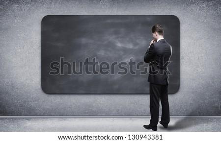 man looking at blackboard in loft interior - stock photo