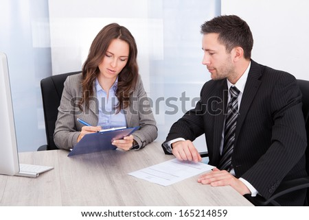 Man Looking At Businessman Writing On Clipboard