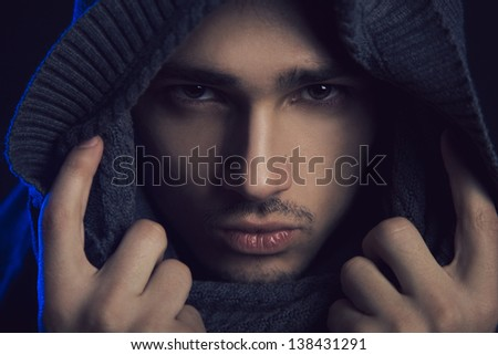Man looking at camera in studio on black background